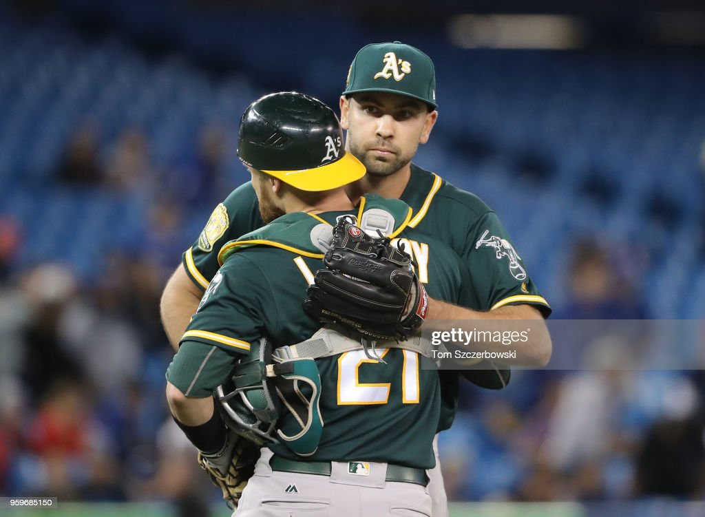 Lou Trivino #62 of the Oakland Athletics celebrates their victory with Jonathan Lucroy #21 during MLB game action against the Toronto Blue Jays at Rogers Centre on May 17, 2018 in Toronto, Canada.