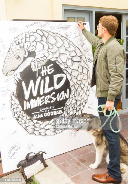 Lou Wegner with Luna the Husky signs artwork by the first virtual reserve Wild Immersion by Jane Goodall at Kids Against Animal Cruelty visits TAP...
