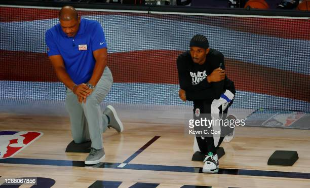 Lou Williams and head coach Doc Rivers of the LA Clippers look on during the national anthem before the start of a game against the Dallas Mavericks...
