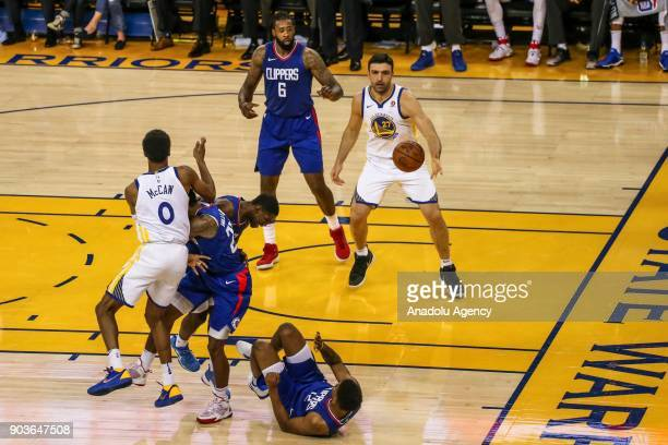 Lou Williams and Tyrone Wallace of LA Clippers in action against Patrick McCaw of Golden State Warriors during the NBA basketball game between LA...