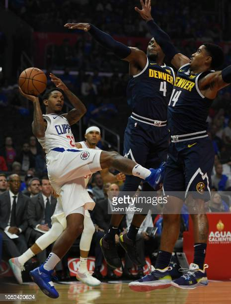 Lou Williams of the LA Clippers looks to pass the ball against Paul Millsap and Monte Morris of the Denver Nuggets in the first half during the...