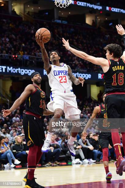 Lou Williams of the LA Clippers shoots over Cedi Osman of the Cleveland Cavaliers during the first half at Quicken Loans Arena on March 22 2019 in...