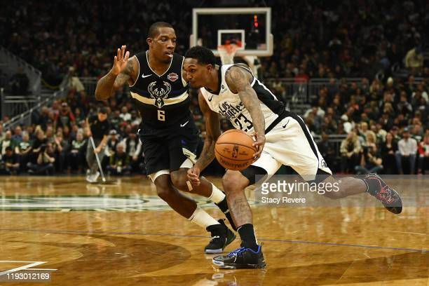 Lou Williams of the Los Angeles Clippers drives around Eric Bledsoe of the Milwaukee Bucks during a game at Fiserv Forum on December 06 2019 in...