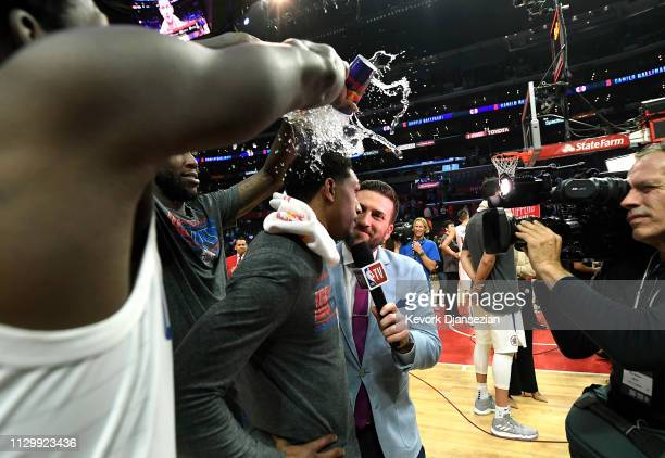 Lou Williams of the Los Angeles Clippers is doused with water by teammates Patrick Beverley and Montrezl Harrell to celebrate after getting the most...