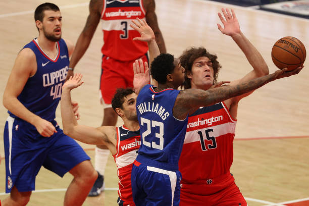 Lou Williams of the Los Angeles Clippers shoots in front of Robin Lopez of the Washington Wizards during the first half at Capital One Arena on March...