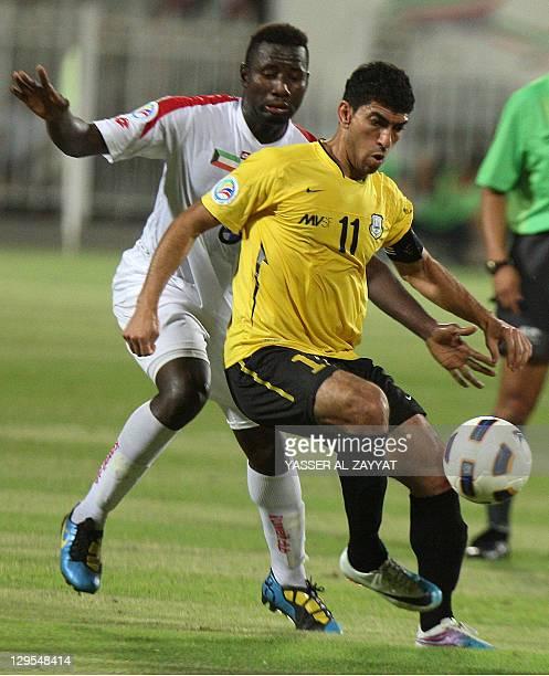 Louai Salah of Iraq's Arbil challenges Kuwait SC's Malian midfielder Lassana Fane during their AFC Cup second leg semifinal football match in Kuwait...