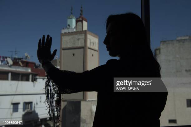 Loubna a 27yearold Moroccan victim of cyberbullying looks out of the window in the coastal city of Casablanca on March 9 2020 In Morocco more than...