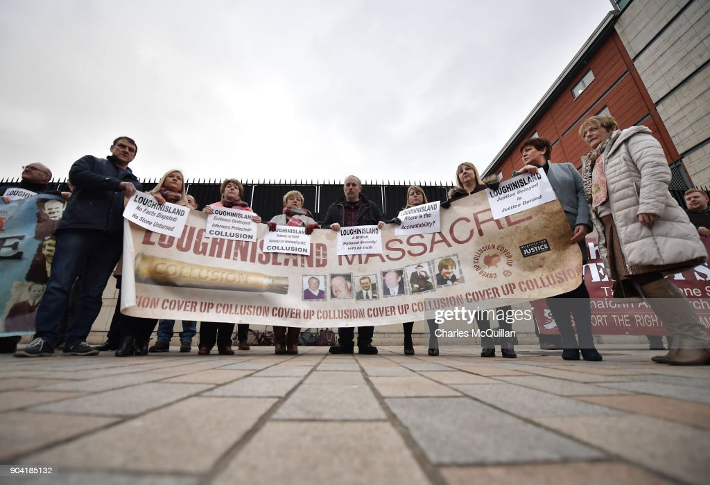 Loughinisland victim family members stand with a banner outside Belfast High Court on January 12, 2018 in Belfast, Northern Ireland. The judge has delayed his ruling on a police ombudsman's report into the murders of six catholic men in 1994 who were shot by loyalist gunmen as they watched a World Cup football match in the Heights Bar in Loughinisland. In June 2016, the police ombudsman ruled there had been collusion between some police officers and the gunmen however in December, a judge ruled that conclusion was 'unsustainable in law'. The case is adjourned until next week following a late change in the police ombudsman's legal team.