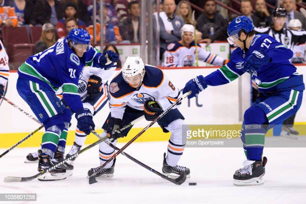 Loui Eriksson and Vancouver Canucks defenseman Ben Hutton defend against Edmonton Oilers right wing Ty Rattie during their NHL preseason game at...