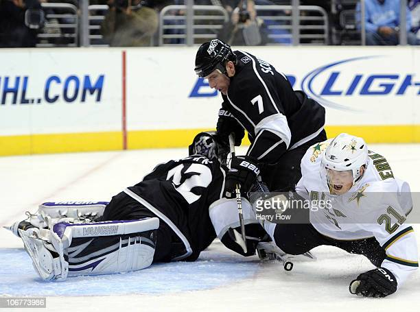 Loui Eriksson of the Dallas Stars is hooked to the ice by Rob Scuderi in front of Jonathan Quick of the Los Angeles Kings during the third period at...