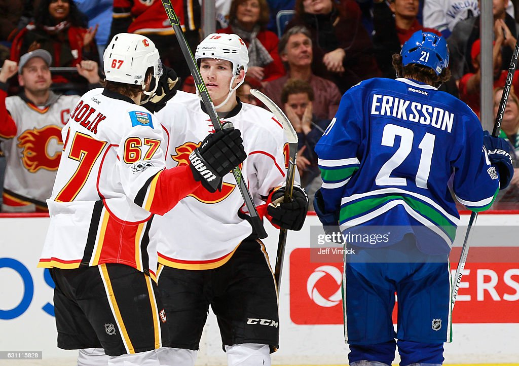 Loui Eriksson #21 of the Vancouver Canucks skates away dejected as Michael Frolik #67 of the Calgary Flames is congratulated by teammate Matthew Tkachuk #19 after scoring during their NHL game at Rogers Arena January 6, 2017 in Vancouver, British Columbia, Canada. Vancouver won 4-2.