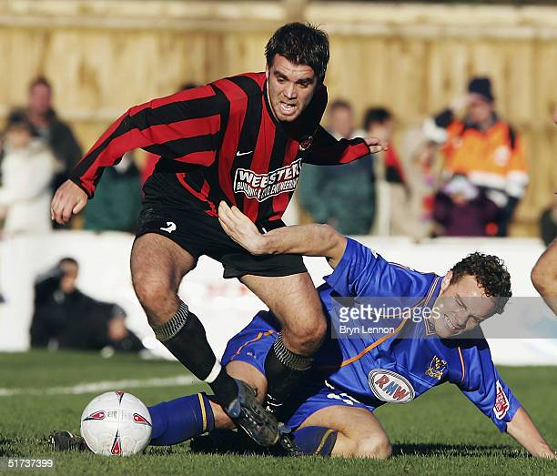 Louie Farrington of Histon tackles Stuart Whitehead of Shrewsbury Town during the FA Cup first round match between Histon FC and Shrewsbury Town at...