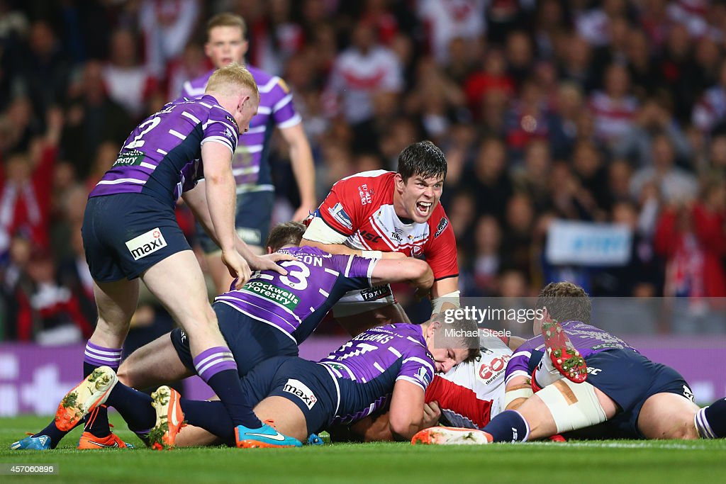 Louie McCarthy-Scarsbrook (C) of St Helens celebrates his sides opening try scored by Sia Soliola (HIDDEN) during the First Utility Super League Grand Final match between St Helens and Wigan Warriors at Old Trafford on October 11, 2014 in Manchester, England.