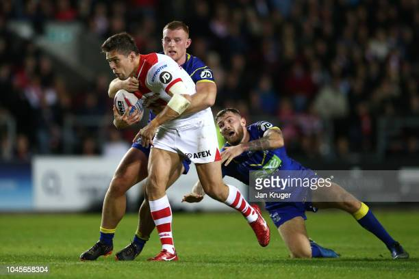 Louie McCarthyScarsbrook of St Helens crashes through the tackle of Jack Hughes and Daryl Clark of Warrington Wolves during the BetFred Super League...