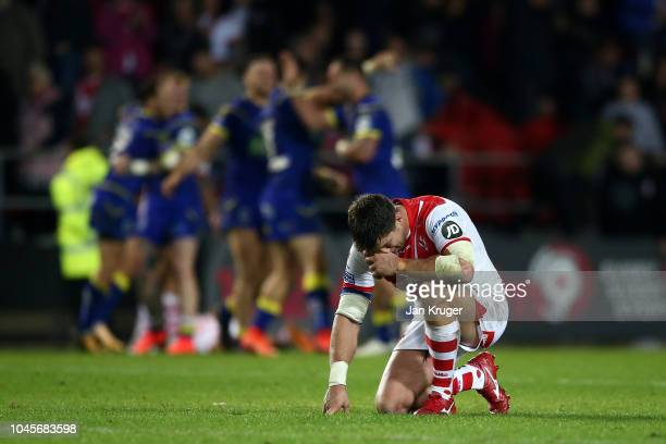 Louie McCarthy-Scarsbrook of St Helens drops to his knees as Warrington Wolves celebrate at the final whistle during the BetFred Super League semi...