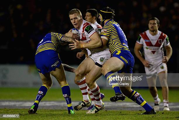Louie McCarthyScarsbrook of St Helens is tackled by Daryl Clark and Chris Hill of Warrington Wolves during the World Club Series match between...