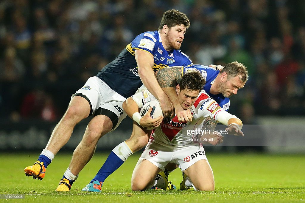 Louie McCarthy-Scarsbrook of St. Helens R.F.C falls from a tackle by Jamie Peacock and Mitch Garbutt of Leeds Rhinos during the First Utility Super League Semi Final between Leeds Rhinos and St Helens at Headingley Carnegie Stadium on October 2, 2015 in Leeds, England.