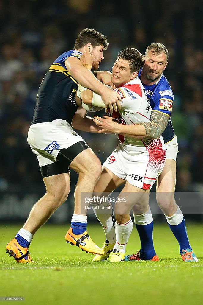 Louie McCarthy-Scarsbrook of St. Helens R.F.C pushes through Jamie Peacock and Mitch Garbutt of Leeds Rhinos during the First Utility Super League Semi Final between Leeds Rhinos and St Helens at Headingley Carnegie Stadium on October 2, 2015 in Leeds, England.