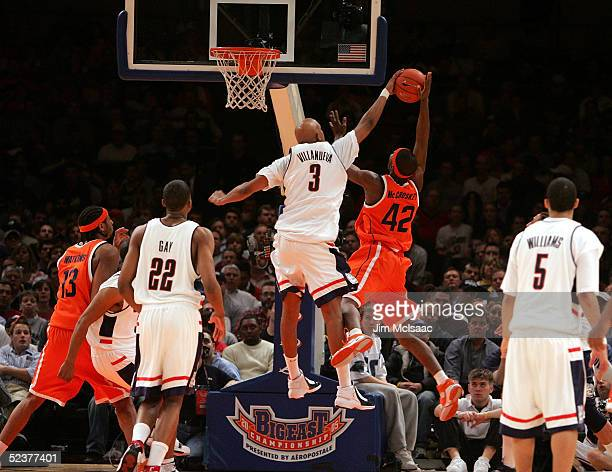Louie McCroskey of the Syracuse Orangemen gets blocked by Charlie Villanueva of the Connecticut Huskies during the semifinal round of the Big East...