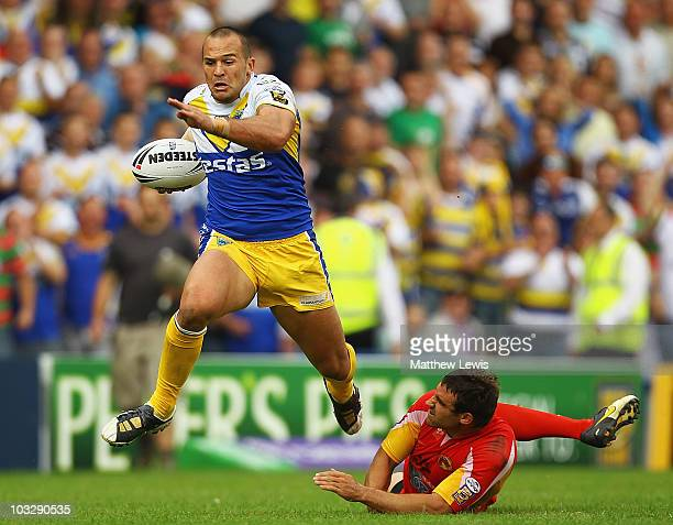 Louis Anderson of Warrington Wolves skips out of the tackle from Thomas Bosc of Catalans on the way to score his third try during the Carnegie...