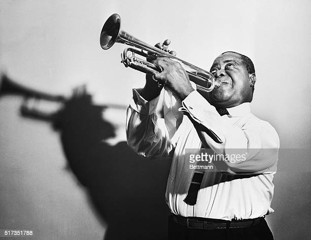 Louis Armstrong blows a horn in a publicity picture