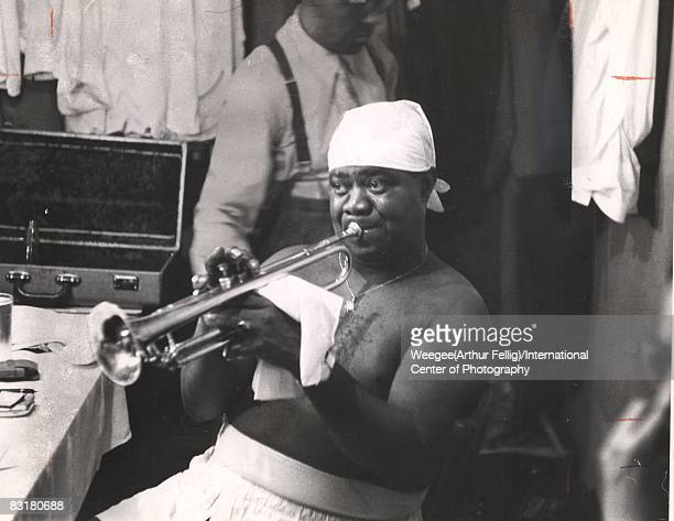 Louis Armstrong jazz musician playing trumpet backstage at the Basin Street night club New York ca1950s Photo by Weegee/International Center of...