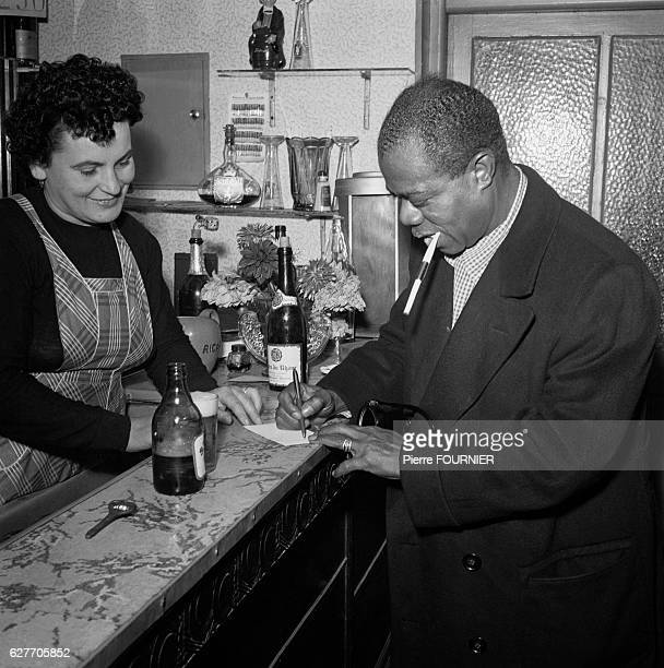 Louis Armstrong signs an autograph in Paris where he is staying for a concert at the Olympia music hall