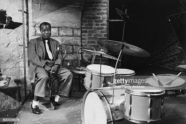 Louis Armstrong sits next to a drum set in 1960 during the filming of 'Paris Blues' in Paris France