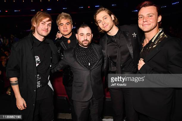 Louis Bell poses with Michael Clifford Calum Hood Luke Hemmings and Ashton Irwin of 5 Seconds of Summer during the 2019 iHeartRadio Music Awards...
