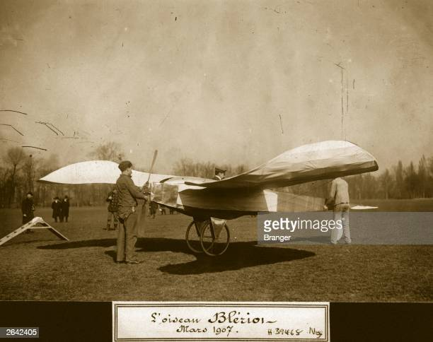 Louis Bleriot French aviation pioneer sits in his Bleriot V 'L'Oiseau' monoplane while mechanics prepare it for flight Aeroplane Album Vol 1 Page 71