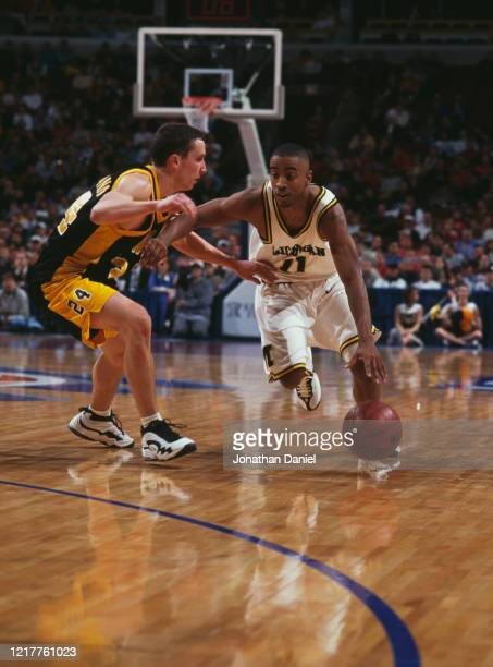 Louis Bullock Guard for the University of Michigan Wolverines dribbles past Ron Oliver of the University of Iowa Hawkeyes during the NCAA Big10...