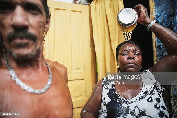 Louis Carlos de Sousa looks on as Tania Gonzalves cools herself off with water from the one running water pipe that serves dozens of residents in a...