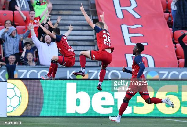 Louis D'Arrigo of Adelaide United celebrates after scoring his teams first goal with Ben Halloran of Adelaide United and Al Hassan Toure of Adelaide...