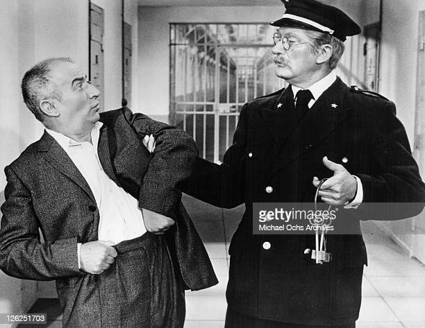 Louis de Funes grabbed by police guard in a scene from the film 'Fantomas' 1964