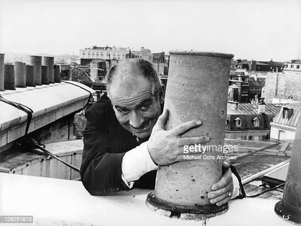 Louis de Funes hanging on chimney in a scene from the film 'Fantomas' 1964