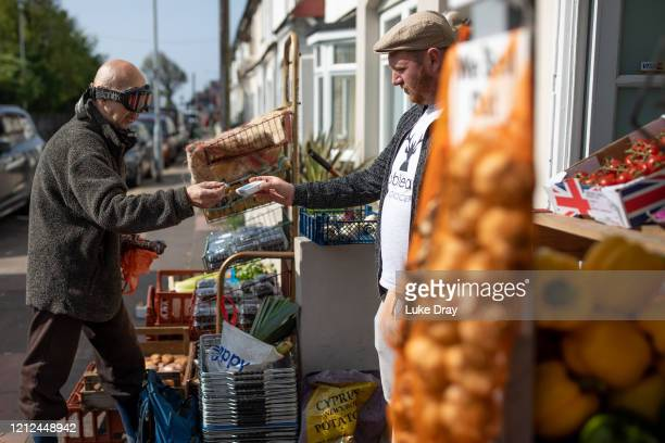 Louis Deblous serves a customer at his greengrocers on May 9, 2020 in Brighton, England. He has been running his business for for eight years, 'Our...