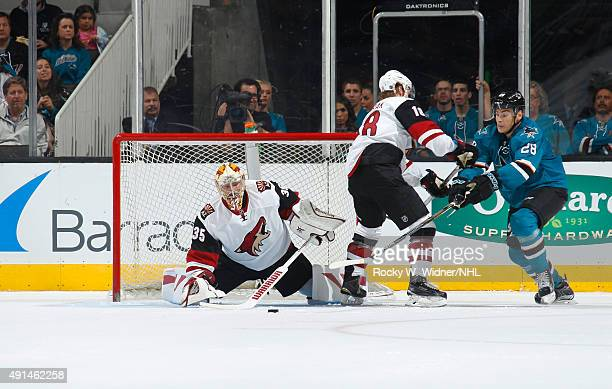 Louis Domingue and Christian Dvorak of the Arizona Coyotes protect the net against Timo Meier of the San Jose Sharks at SAP Center on September 25...