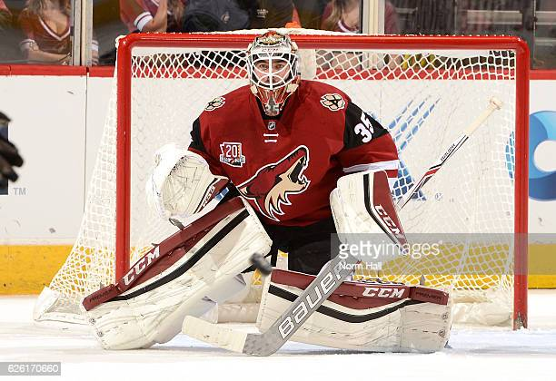 Louis Domingue of the Arizona Coyotes keeps his eye on the puck while getting ready to make a save against the Vancouver Canucks at Gila River Arena...