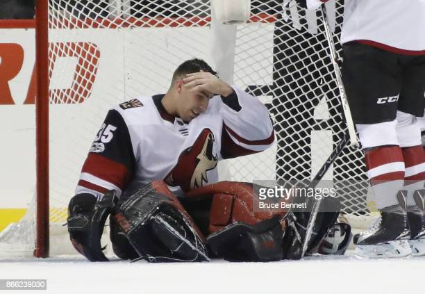 Louis Domingue of the Arizona Coyotes reacts after being hit in the mask by the skate of Mathew Barzal of the New York Islanders at the Barclays...