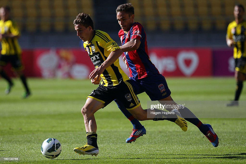 Louis Fenton of the Phoenix runs the ball under pressure from James Brown of the Jets during the round 18 A-League match between the Wellington Phoenix and the Newcastle Jets at Westpac Stadium on January 27, 2013 in Wellington, New Zealand.
