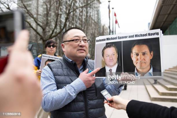 Louis Huang of Vancouver Freedom and Democracy for China holds photos of Canadians Michael Spavor and Michael Kovrig, who are being detained by...