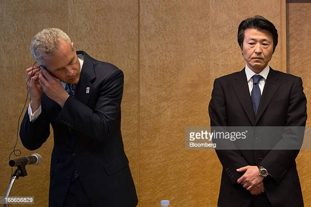 Louis J. Forster, senior managing director of Cerberus Capital Management LP, left, adjusts his earpiece while Yoshiteru Suzuki, president of...