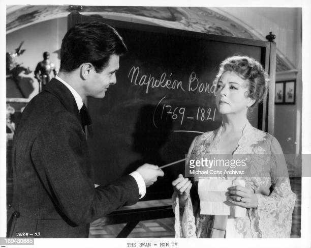 Louis Jourdan and Jessie Royce Landis in front of chalk board in a scene from the film 'The Swan' 1956