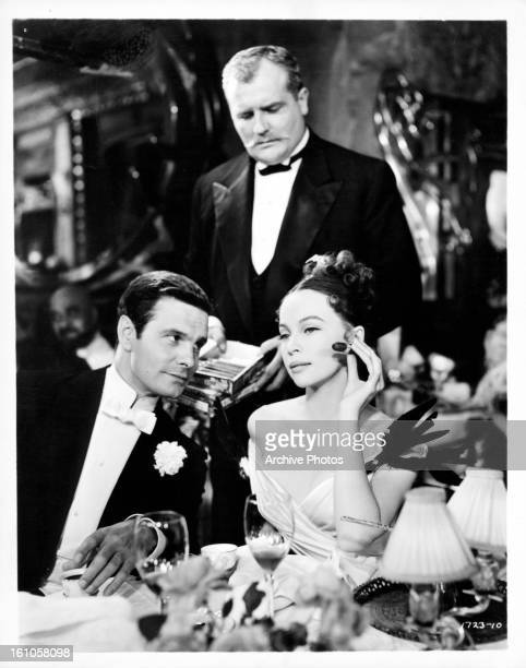 Louis Jourdan and Leslie Caron at a formal dinner in a scene from the film 'Gigi' 1958