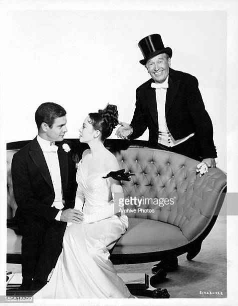 Louis Jourdan and Leslie Caron on couch with a smiling Maurice Chevalier behind them in publicity portrait for the film 'Gigi' 1958