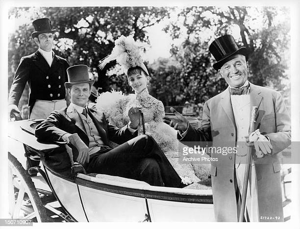 Louis Jourdan and Leslie Caron sitting in a carriage with Maurice Chevalier in a scene from the film 'Gigi' 1958