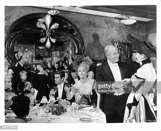 Louis Jourdan Eva Gabor and Maurice Chevalier in packed dining room in a scene from the film 'Gigi' 1958