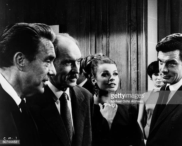 Louis Jourdan finally meets Edmond O'Brien as Senta Berger looks on in a scene from the movie To Commit a Murder circa 1967