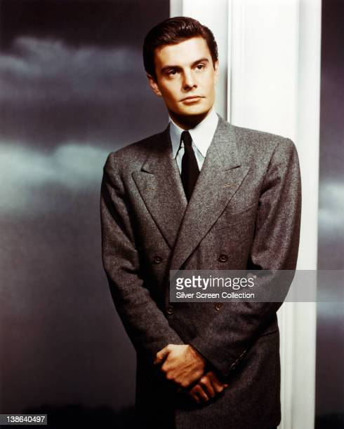 Louis Jourdan French actor wearing a dark grey suit with a white shirt and a black tie in a studio portrait circa 1960