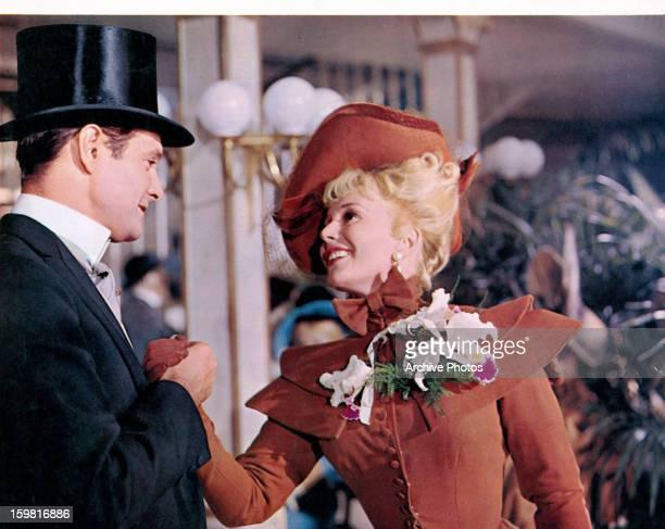 Louis Jourdan grabbing the hand of Leslie Caron in a scene from the film 'Gigi' 1958